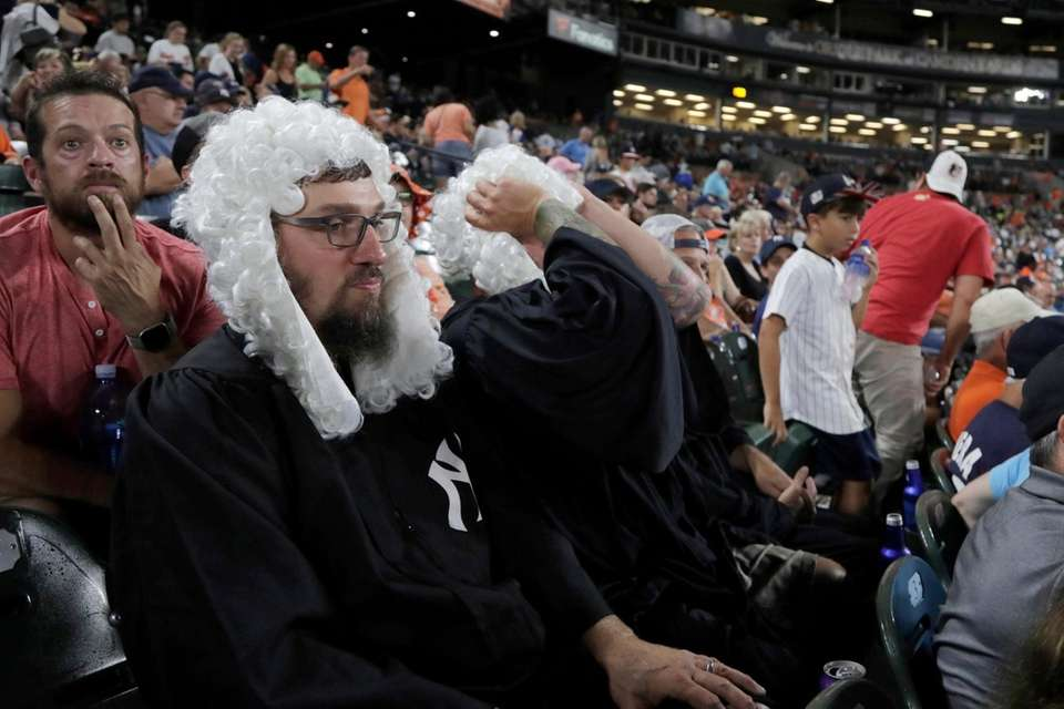 Spectators wear costumes supporting New York Yankees right