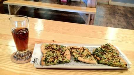 """The """"brewtique crustique"""" is topped with pesto, pine"""
