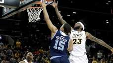 Rhode Island's Omar Silverio drives past VCU's Issac