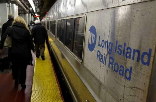 Customers walk by an LIRR train at Penn