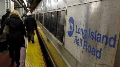 Customers walk by an LIRR train at Penn