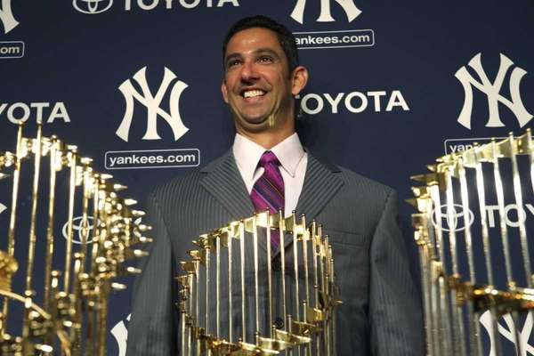 Jorge Posada smiles while standing behind the five