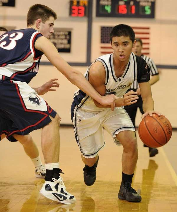 Stony Brook's Marco Masakayan is fouled by Smithtown