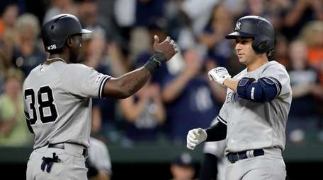 Yankees' Kyle Higashioka, right, is greeted at home