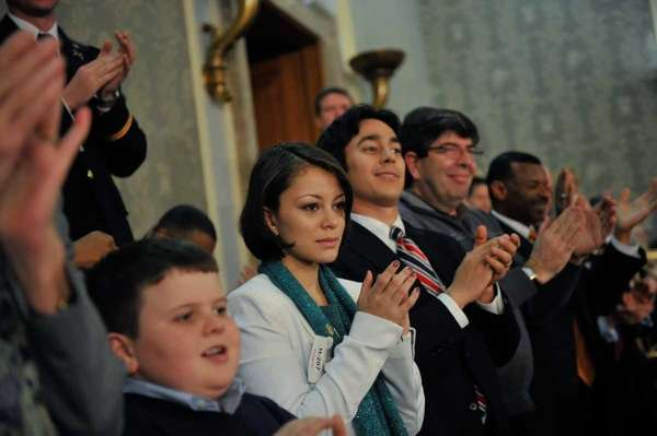 Samantha Garvey listens and applauds as President Obama