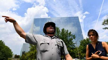 A police officer redirects members of the media
