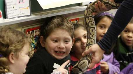 Kindergartner David Alvarez, center, reacts as his classmate,