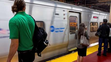 Long Island Rail Road commuters stand by as