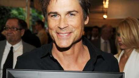 Actor Rob Lowe poses with the year of