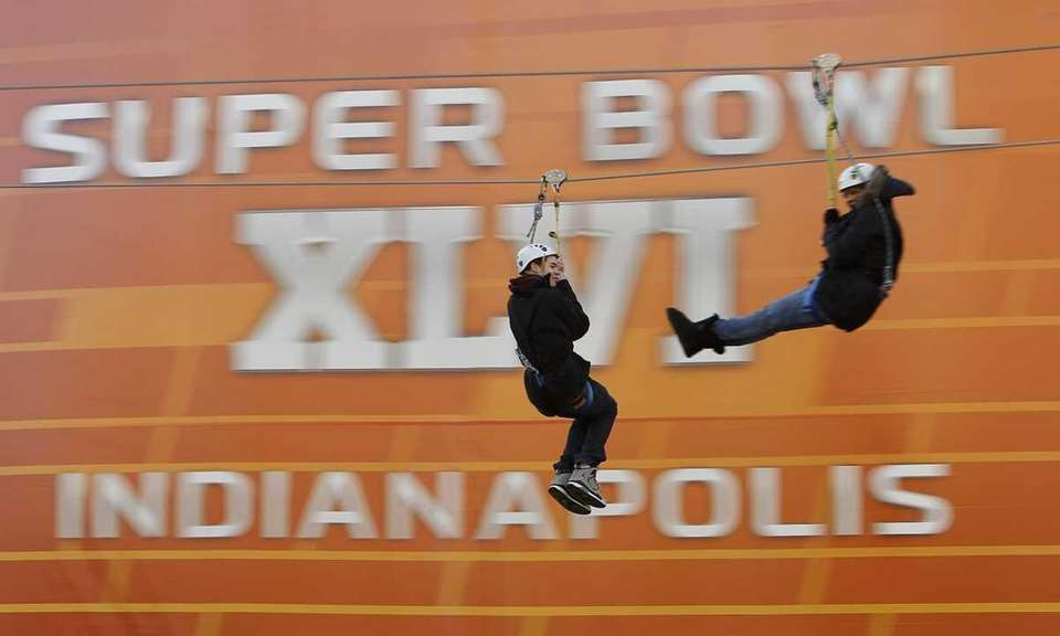 Fans ride a zip line during the NFL
