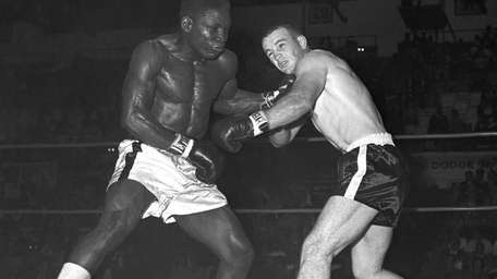 Former middleweight champion Dick Tiger, left, shakes up