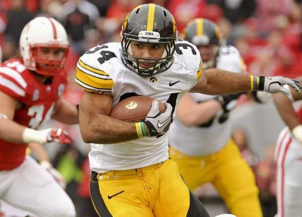 Iowa's Marcus Coker runs the ball past Nebraska's
