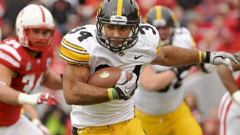 Iowa's Marcus Coker runs the ball past Nebraska's