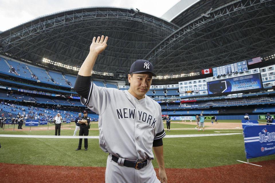 Yankees pitcher Masahiro Tanaka waves to fans as