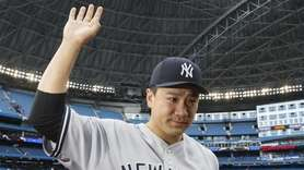 Yankees pitcher Masahiro Tanaka waves to fans as