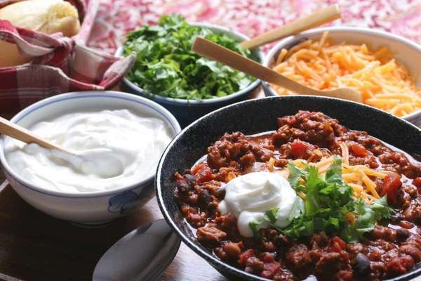 Beef and kidney bean chili with garnishes cheese,