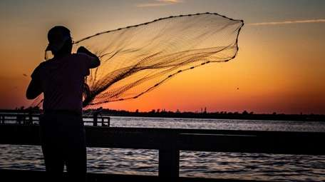 A woman tossing a fishing net into the