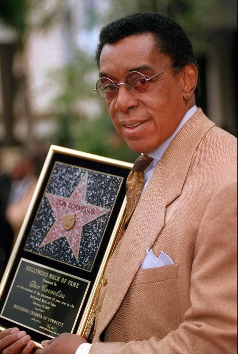 Television producer Don Cornelius holds a plaque on