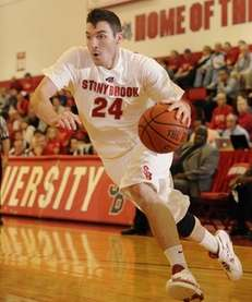 Stony Brook guard Tommy Brenton drives hard along