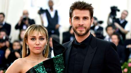 Miley Cyrus, left, and Liam Hemsworth attend