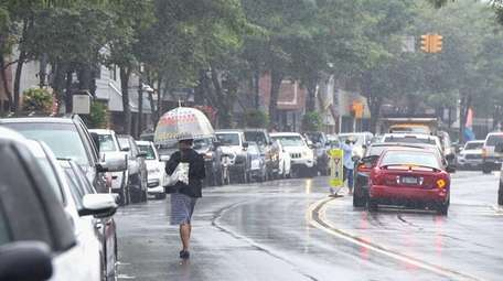 A woman shields herself from the rain near