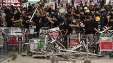 Pro-democracy protesters use baggage carts Tuesday to block