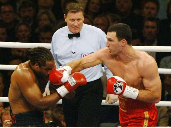 Wladimir Klitschko of Ukraine, right, punches title defender