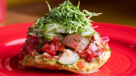 A creamy-crispy avocado tostada stacked with avocado hummus,