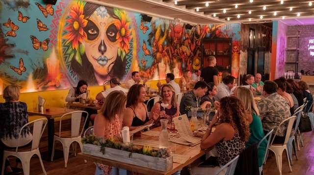 Patrons dine together at a long communal table