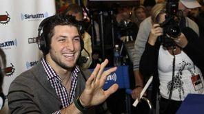 Denver Broncos quarterback Tim Tebow waves to actress