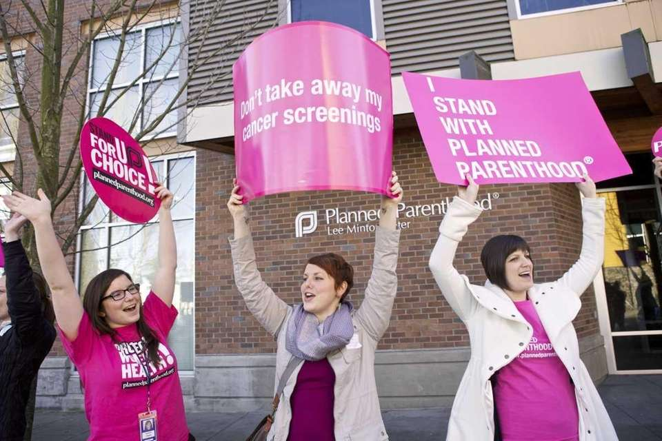 Planned Parenthood supporters hold up signs following a