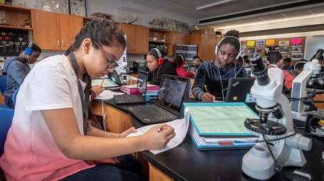 Seventh-grade honors Earth Science student Clohie Clarke, left,