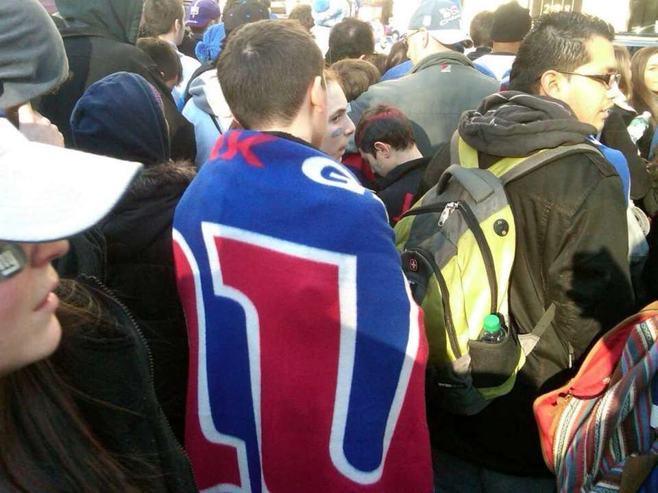 A Giants fan keeps warm before the parade.