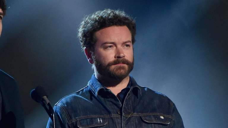 Danny Masterson presents an award onstage during the