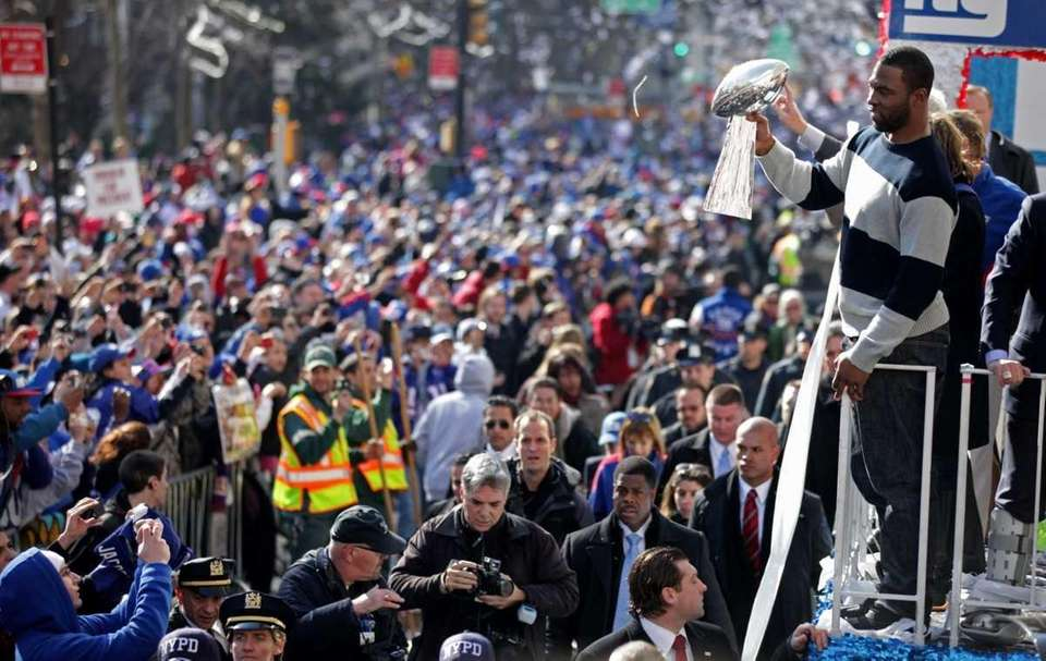 Justin Tuck holds the Lombardi Trophy as the