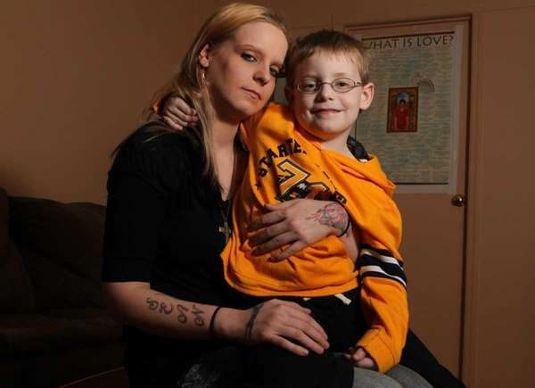 Crystal Feldt (left), of Westbury, holds her son,