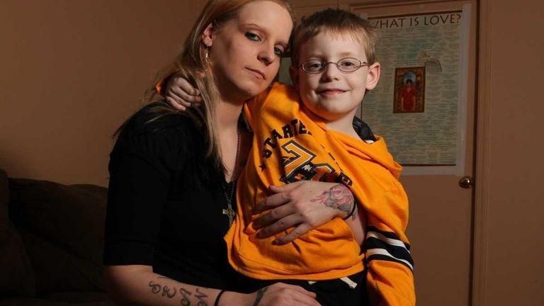 Crystal Feldt (left), of Westbury, holds her son,