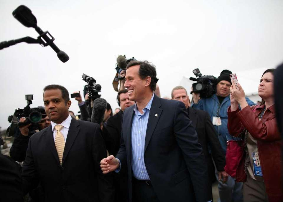 Republican presidential candidate Rick Santorum, center, leaves the