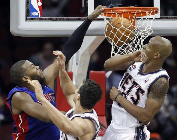 Detroit Pistons' Greg Monroe, left, dunks over New