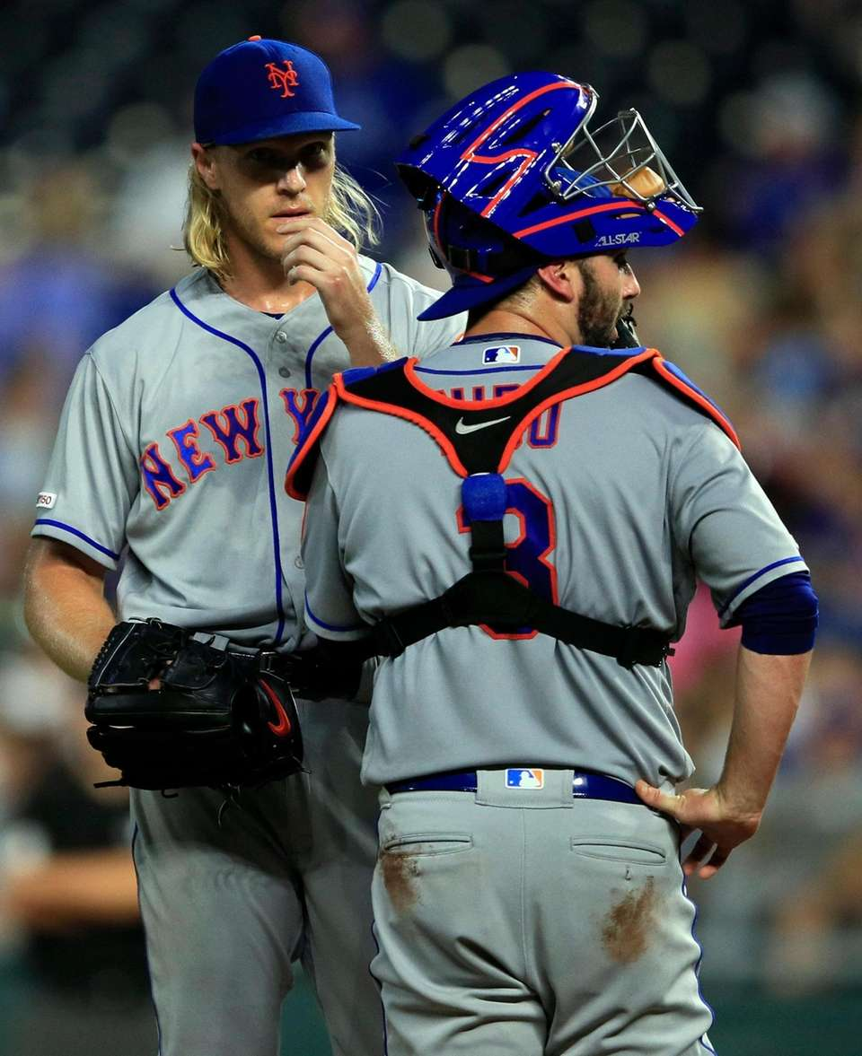 Mets starting pitcher Noah Syndergaard, left, talks with