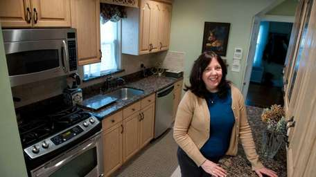 Linda Breeds stands in her Woodmere kitchen, surrounded