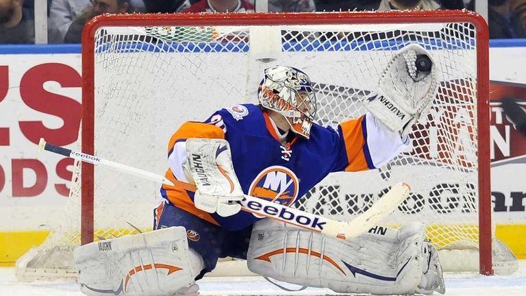 Islanders goalie Evgeni Nabokov makes a glove save.
