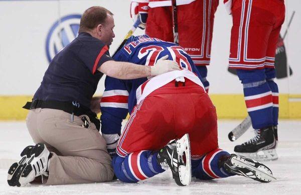 A trainer, left, checks on Rangers' Ruslan Fedotenko