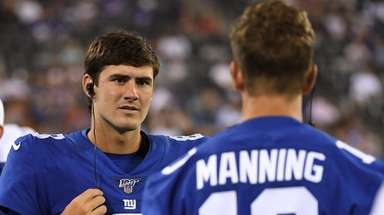 Giants quarterback Daniel Jones talks to quarterback Eli