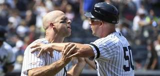 Yankees first base coach Reggie Willits holds back