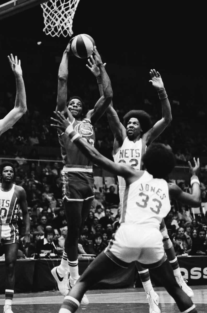 Nets' star Julius Erving jumps to block a