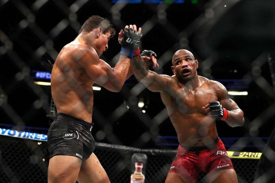 Yoel Romero throws a punch at Paulo Costa