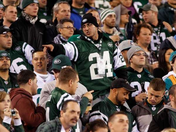 A Jets fan points toward Miami Dolphins fan