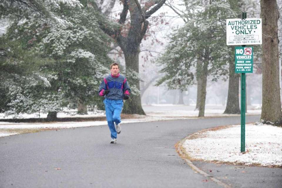 Snow falls on a runner at Eisenhower Park