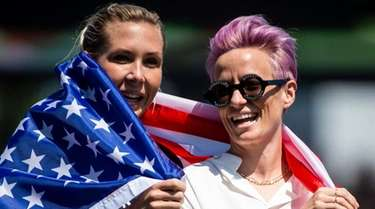 Reign FC midfielder Allie Long, left, and forward